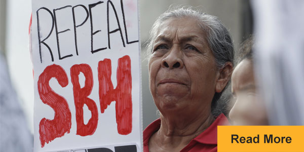 Woman holding sign: Repeal SB4