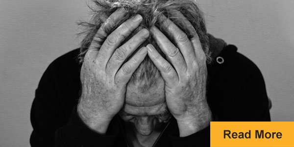 stressed man holding head in hands