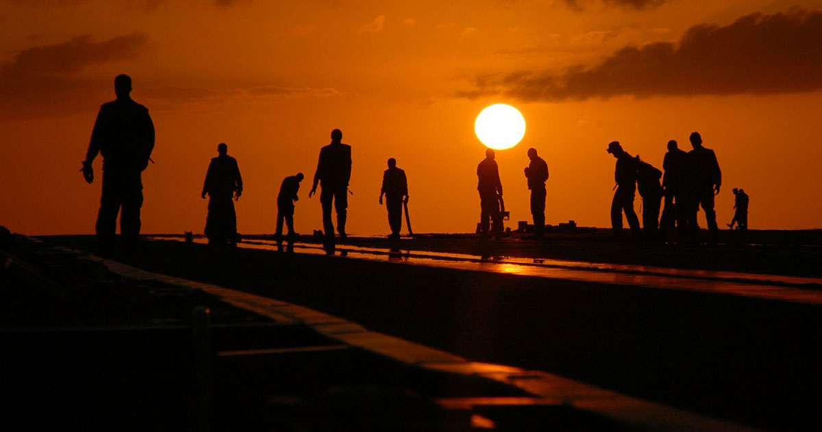 Workers in the field at sunset
