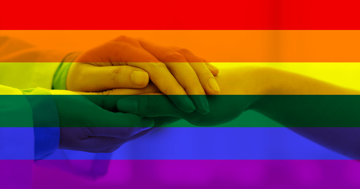 physician holding patients hand with pride flag behind