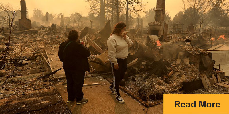 Two women examine the wreckage of wildfire destroyed homes