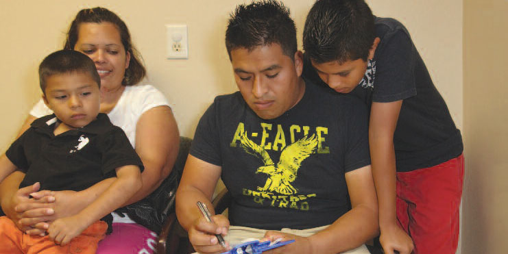 man filling out paperwork in clinic with family