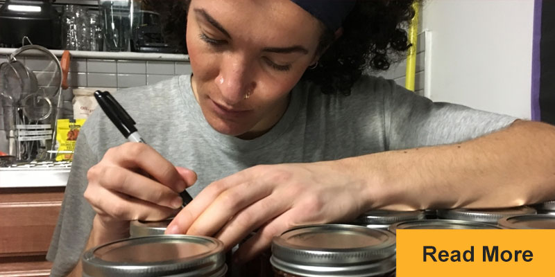 person writing messages on mason jars