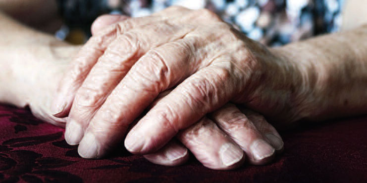 hands of older woman resting on table