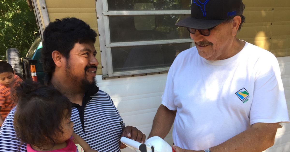 Joel Pelayo giving water cooler to migrant worker