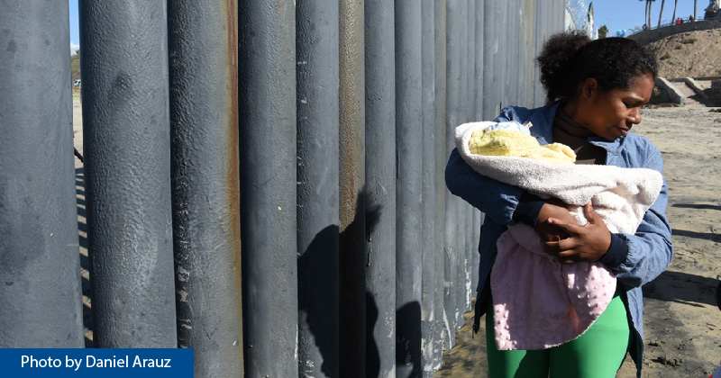 An asylum seeker walks along the border