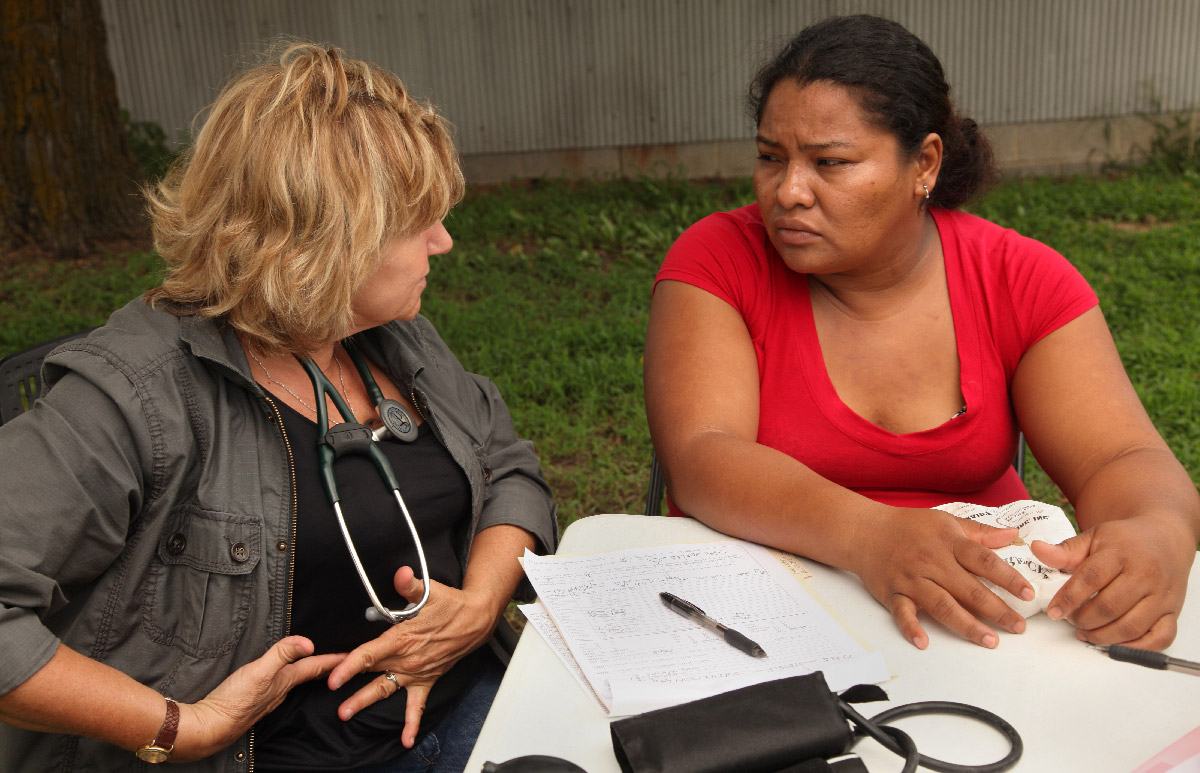 Clinician talks with patient in the field