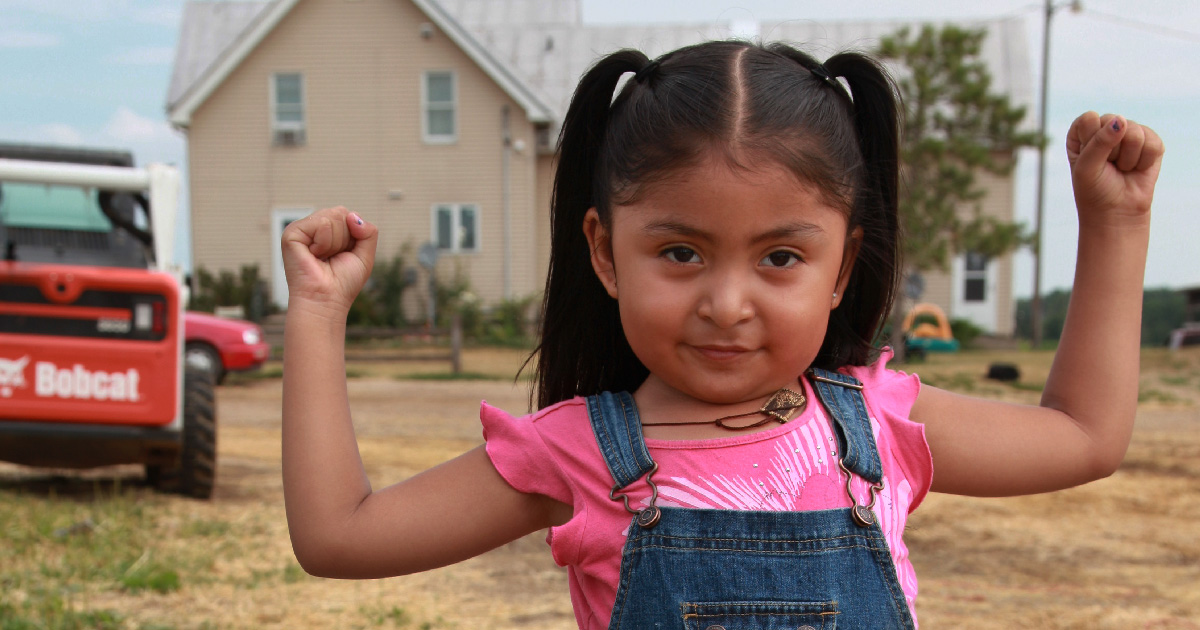 A girl flexes her arms to show strength