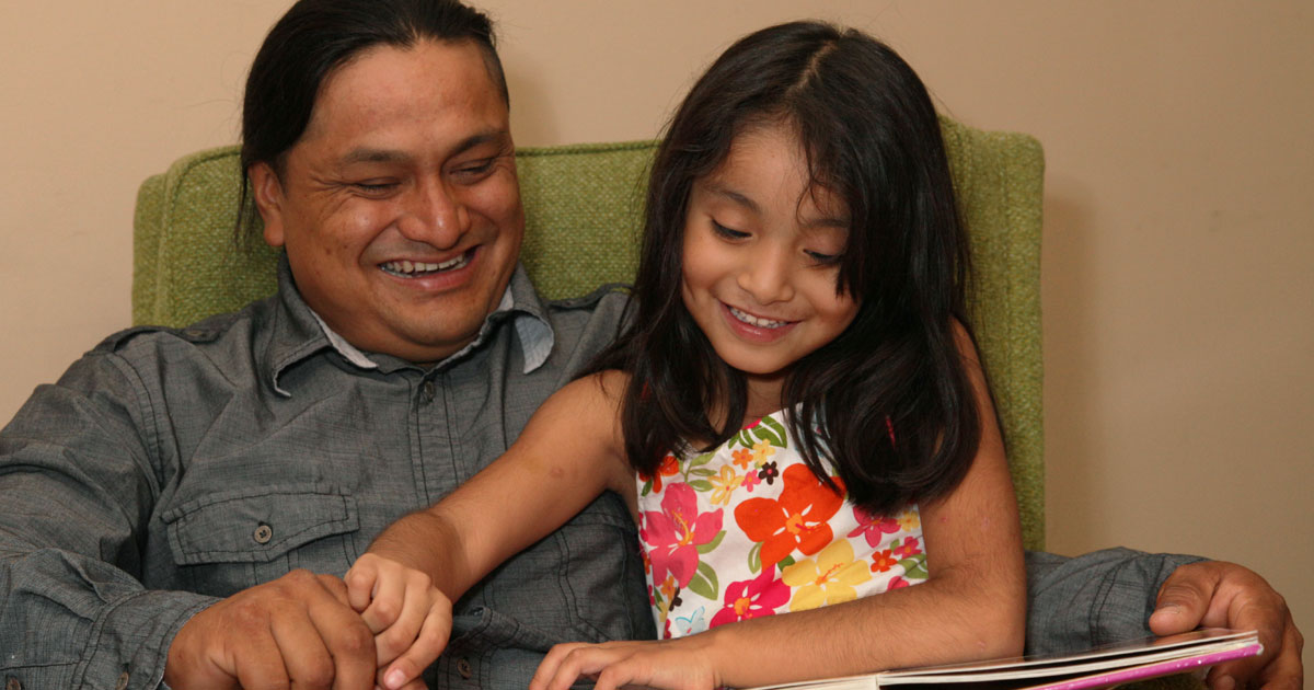 child reading a book with her dad