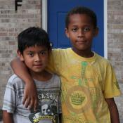 two children standing in front of a brick building