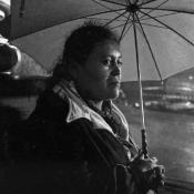 Woman looks out from under umbrella in the rain.