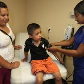 Mother watches as son has blood pressure taken by clinician
