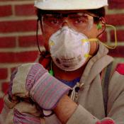 A worker wearing a mask and protective gear