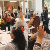Women raise their hands as part of a presentation at the Women's Conference