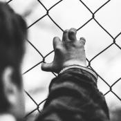 Child holding on to wire fence