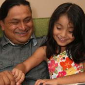 child reading book with her dad