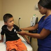 Clinician taking child's blood pressure