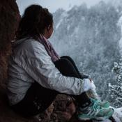 migrant woman looking out over snow covered forest
