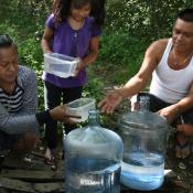 Family gathers water in the forest