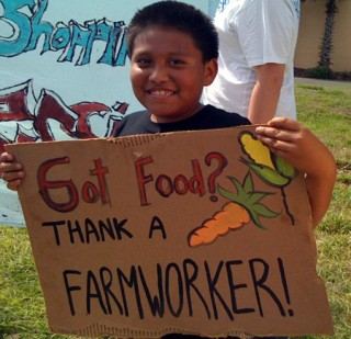 Child holding sign promoting farmworkers