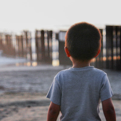 Child stares at border fence
