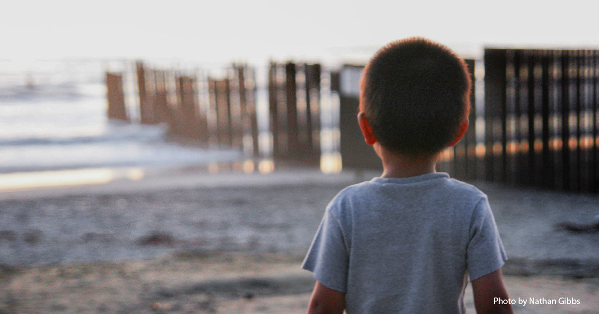 Child looks at border fence