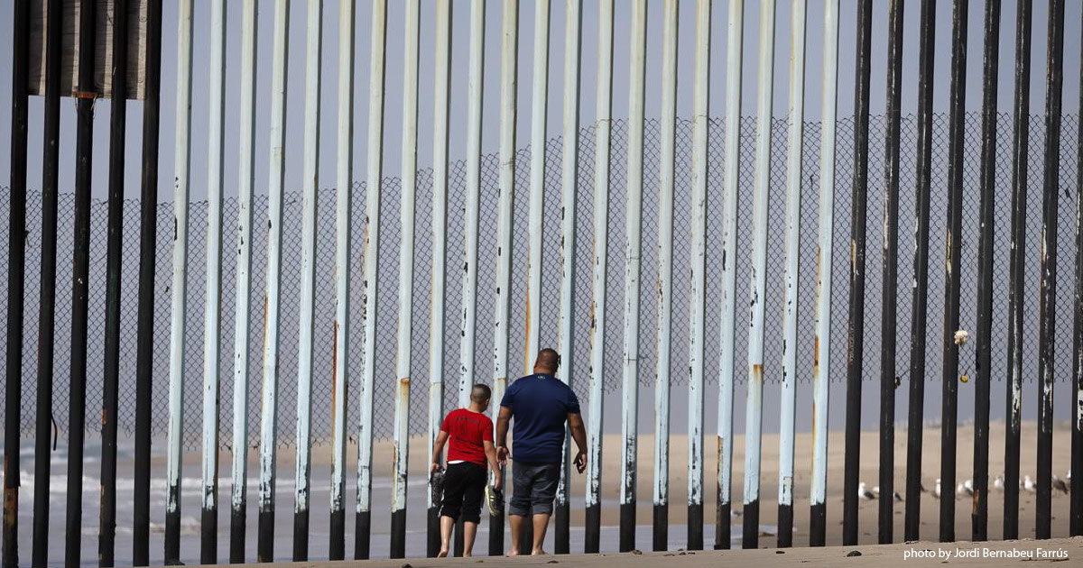 Man and child look through border fence