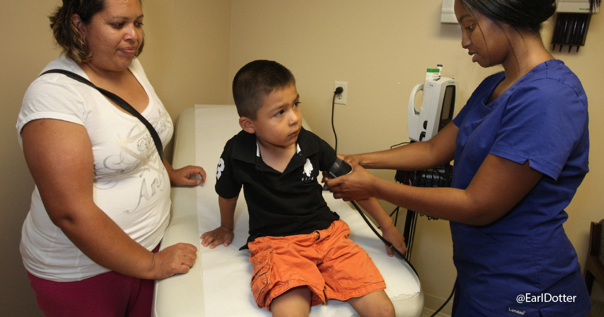 Mother watches son have blood pressure taken by clinician