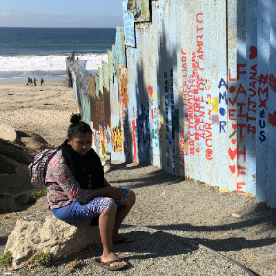 Woman sits on Mexican side of the border