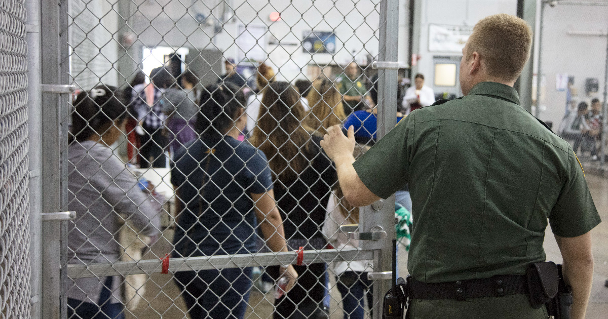 CBP officer lets detainees out of holding area.
