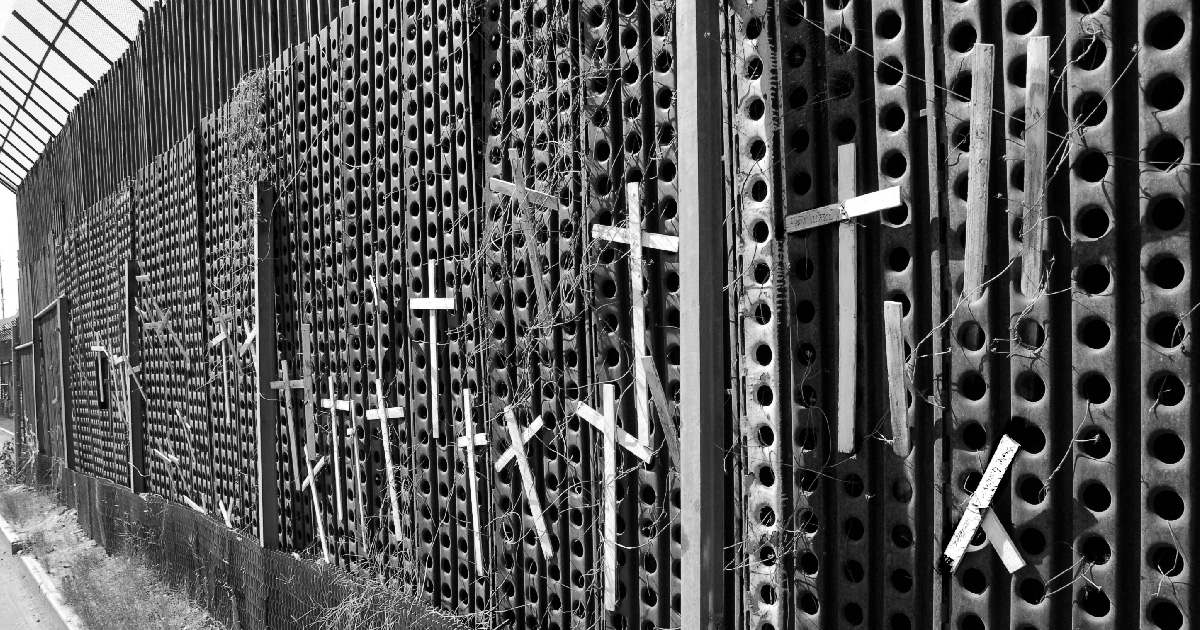 A wall on the US-Mexico border with crosses attached to it.