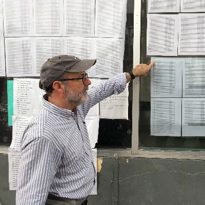 Mike Seifert looks at list of names of immigrants waiting to cross the border.