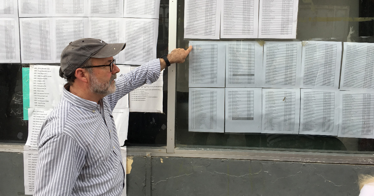 Mike Seifert points at lists of names of those waiting to be called to cross border legally