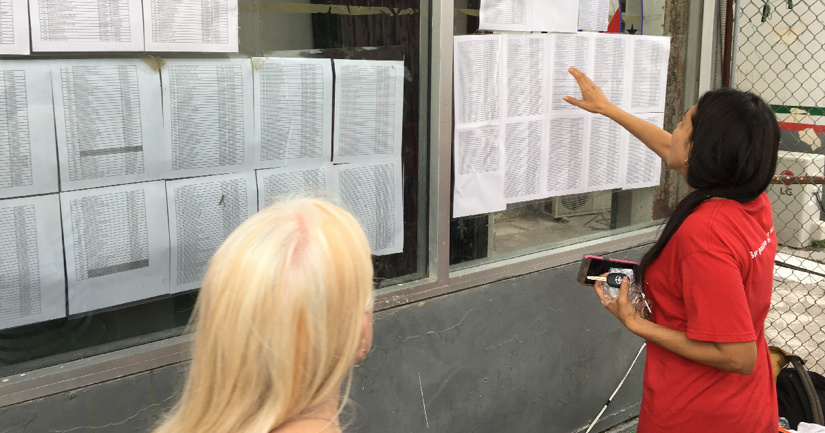 People check lists of names of immigrants in line to apply for entry to the U.S.