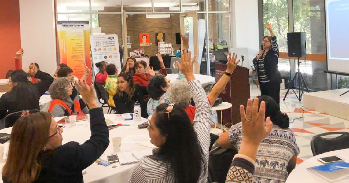 Participants raise hands as part of presentation at 5th annual women's conference