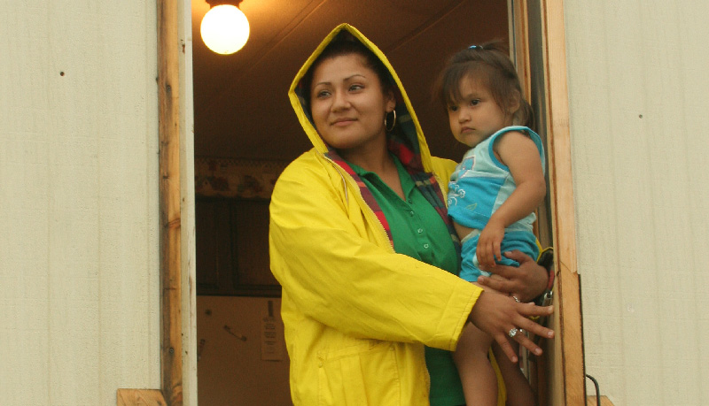 Woman stands in raincoat with young daughter