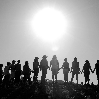 People standing together on hillside under sun