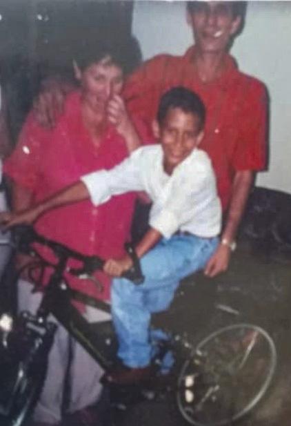 Saul Delgado as a kid posing for a photo with his parents