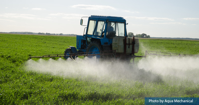 A vehicle spraying pesticides on a field