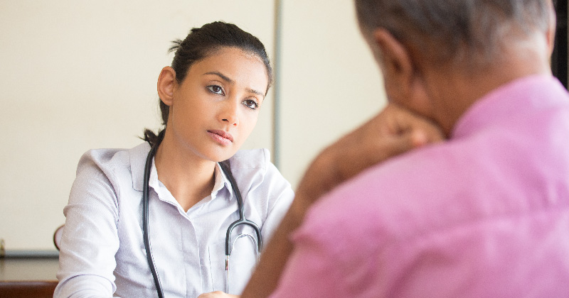 A clinician talks with patient
