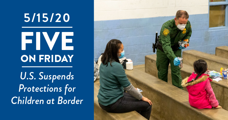 A border patrol officer hands food to a child in a detention facility