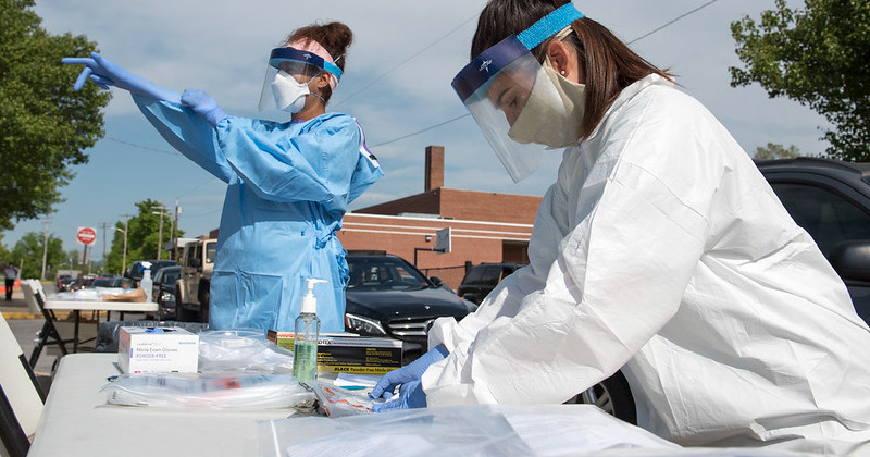 Clinicians put on PPE to prepare for outreach and testing