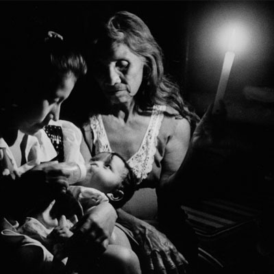 mother feeds baby by candlelight