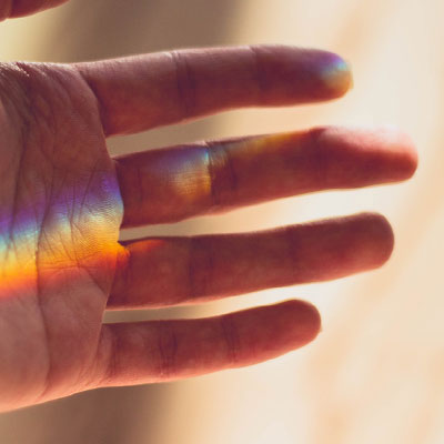hand outstretched with rainbow light