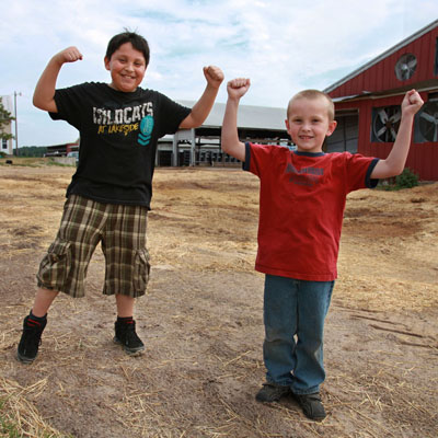 Two kids posing for a photo on a farm