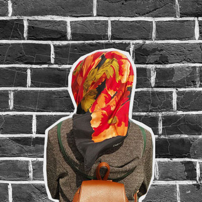 woman in hijab from behind facing brick wall with united states map