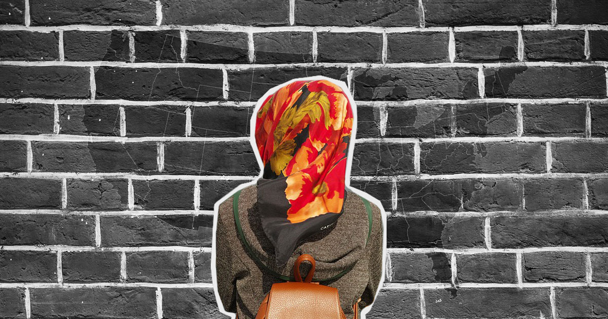 woman in hijab from behind facing brick wall